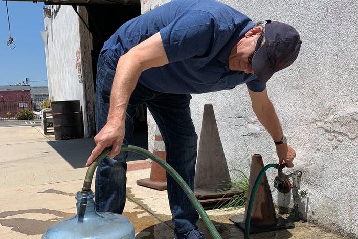 Nicholas E taking water sample in Compton700x467